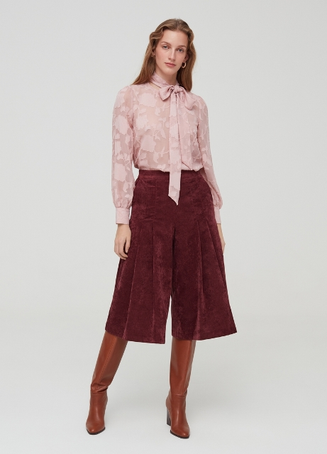 With pale pink blouse and brown leather high boots
