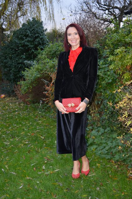 With red blouse, black velvet blazer, red clutch and red shoes
