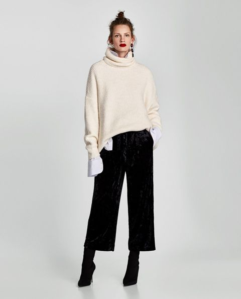 With white long sleeved shirt, beige turtleneck sweater and black sock boots