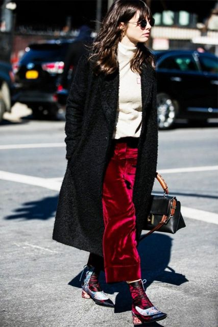 With white turtleneck, black midi coat, bag and colorful printed boots
