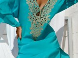 a turquoise mini dress with a coral print plunging neckline and long sleeves is very chic and bold