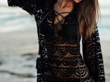 a black boho lace semi sheer mini dress with a laced up neckline and bell sleeves is a trendy item to wear at the beach