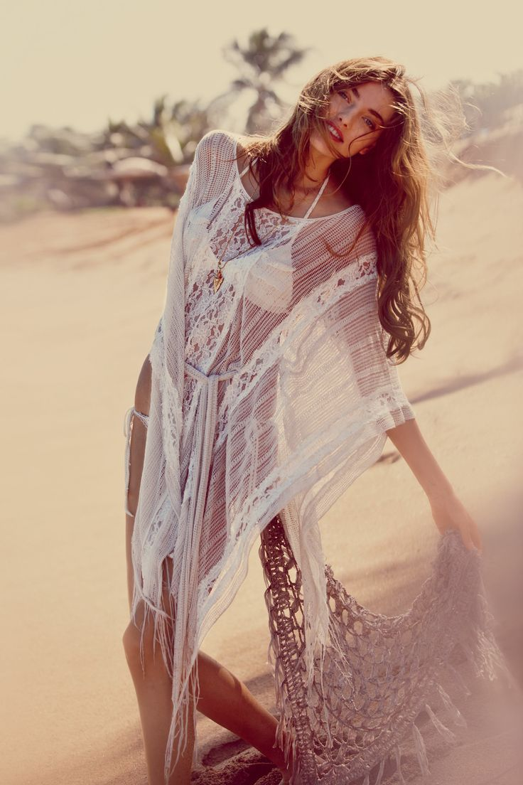 a white semi sheer boho lace coverup with a train is a cool boho beach piece