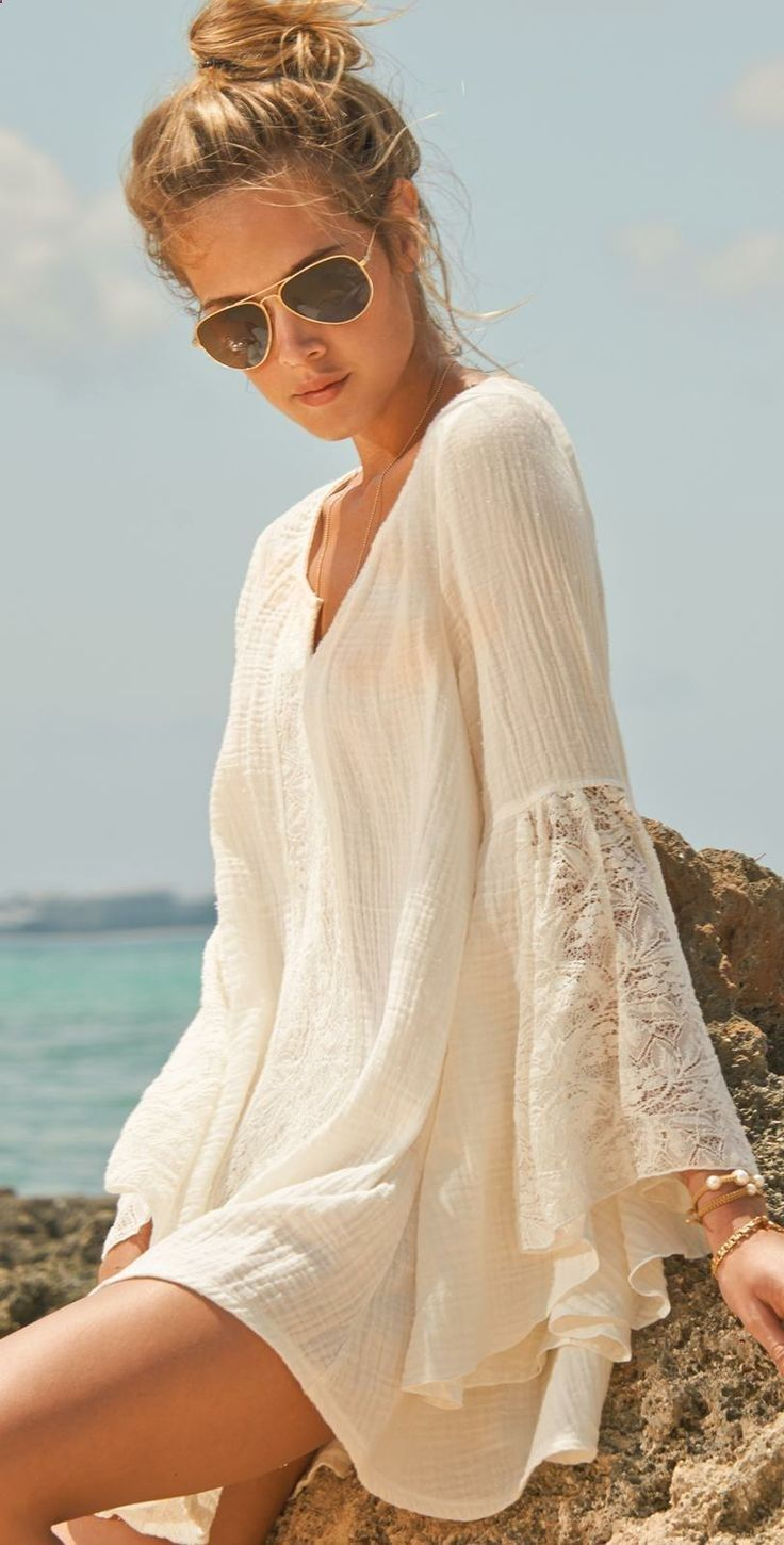 a simple white mini dress with bell lace sleeves and a V neckline is a cool and cute coverup for the beach
