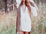 a white lace mini dress, a printed waistcoat, layered necklaces for a 70s inspired boho look