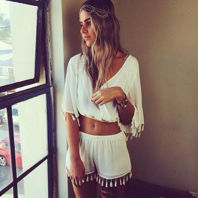 a white boho outfit with a crop top with bell sleeves and shorts wihth tassels plus a boho headpiece