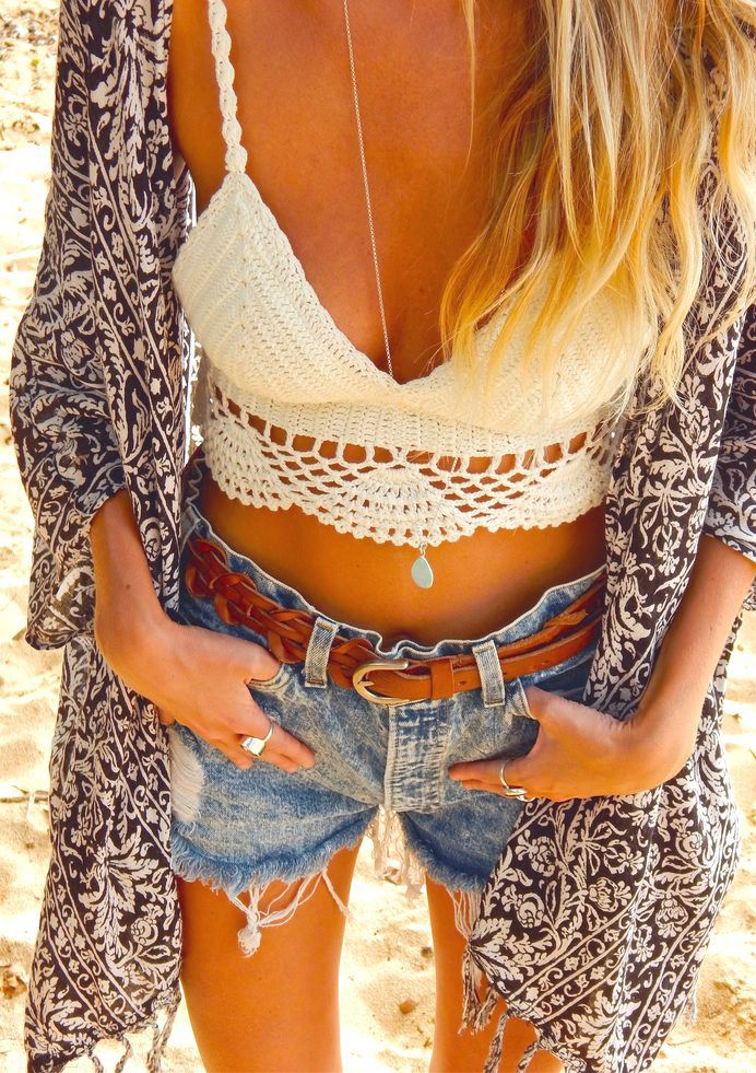 a white crochet crop top, denim shorts, a printed coverup and a necklace