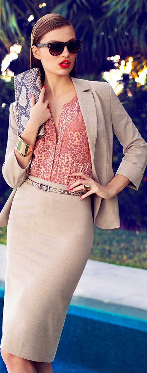 a tan midi skirt suit with a red animal print shirt, a statement bracelet and a snakeskin clutch