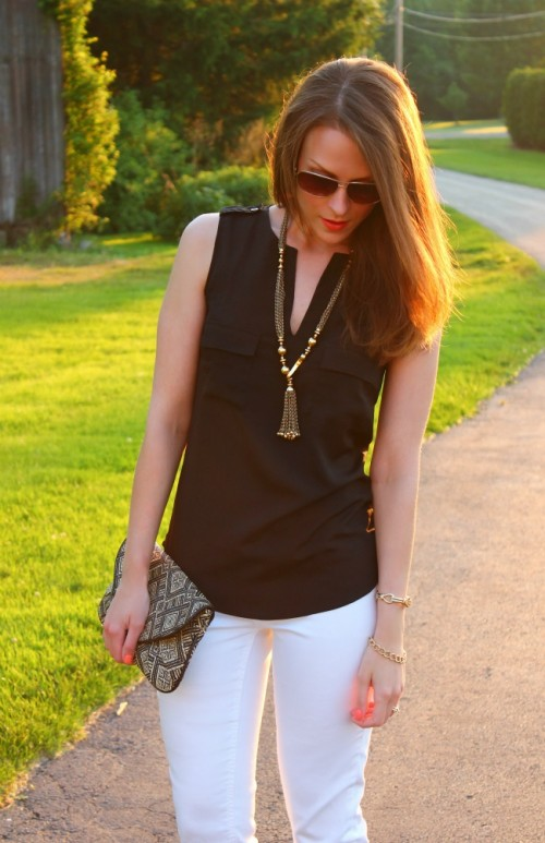 a black sleeveless shirt, white jeans, a statement necklace and an embellished clutch