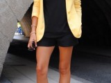 a black top, black shorts, a sunny yellow blazer, black and brown shoes plus layered necklaces
