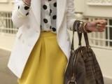 a black and white polka dot blouse, a mustard A-line mini, a creamy long blazer and a brown bag