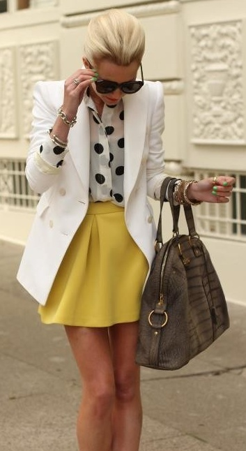 a black and white polka dot blouse, a mustard A line mini, a creamy long blazer and a brown bag