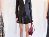 a black suit with an A-line pleated mini, a white shirt, a fuchsia bag and snakeskin print shoes