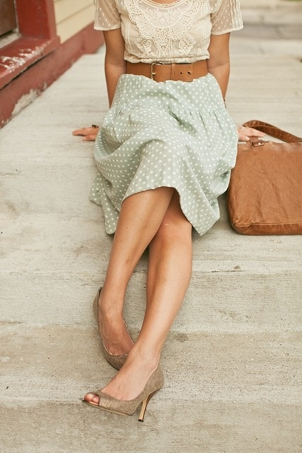 a neutral lace top with short sleeves, a mint polka dot midi, a brown tote and dark glitter shoes