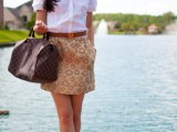 a white short sleeve shirt, a printed mini skirt, tan shoes, a brown bag and a statement necklace
