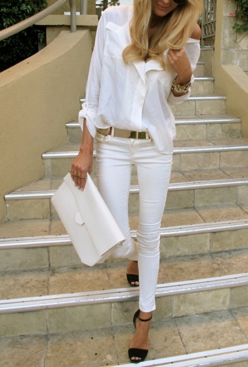 a white oversized shirt, white jeans, black heels, a metallic belt and a white clutch