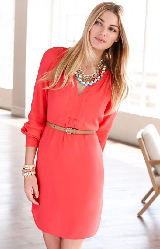 a coral knee dress with long sleeves, a V neckline, layered necklaces, a belt and stacked bracelets
