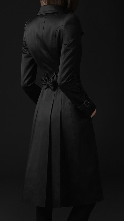 a classic black midi fitting trench with a bow on the back is a stylish piece to wear in any spring or fall