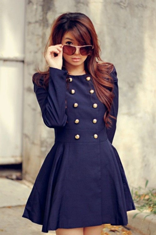 a navy A-line mini dress with gold buttons is a refined retro piece to wear anytime