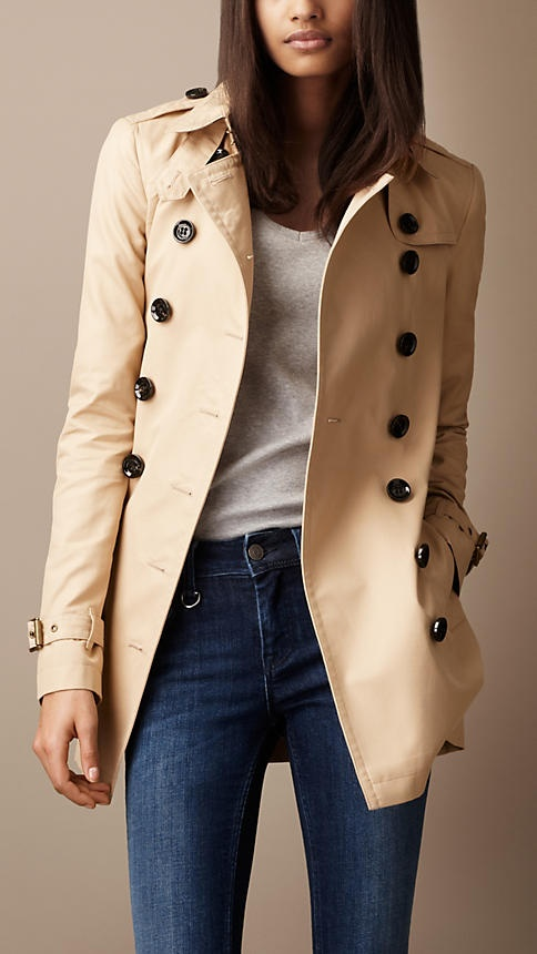 a classic short neutral double-breasted trench with black buttons is a stylish piece to wear this spring
