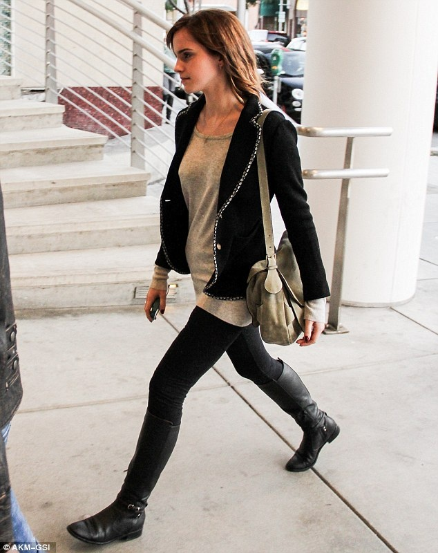 a long grey top, black skinnies, black tall boots, a black embellished blazer and a grey bag