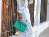 a white maxi dress with purple splashes, layered bracelets and an emerald clutch for a special occasion