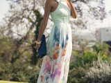 a neutral floral print maxi dress with a halter neckline and a bright clutch for a bold summer look