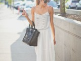 a white boho maxi dress with a lace and embellished bodice, spaghetti straps and a black tote