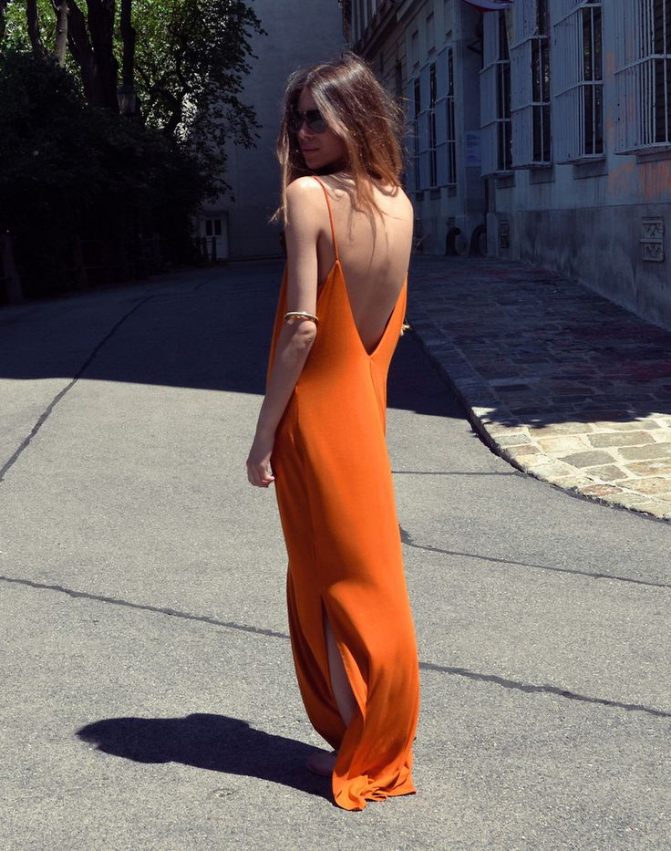 an orange slip maxi dress with an open back with side slits looks chic, bold and cool