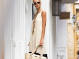 a color block black and white A-line maxi dress with a high neckline, layered necklaces, black flipflops and a woven bag