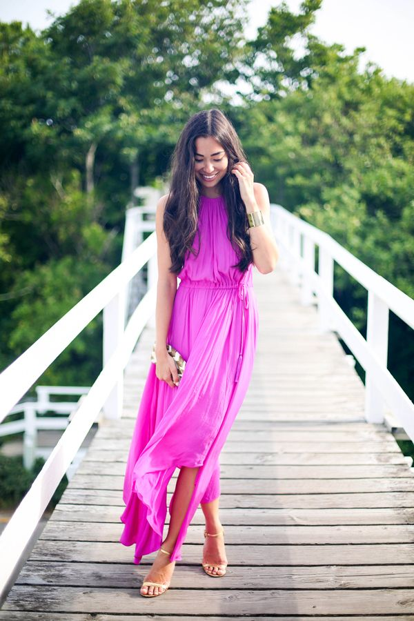a hot pink halter neckline maxi dress, tan heels and a shiny clutch for a special occasion in summer
