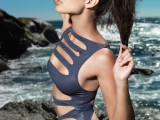 a graphite grey one piece swimsuit with lots of cutouts and no sleeves is sexy and chic