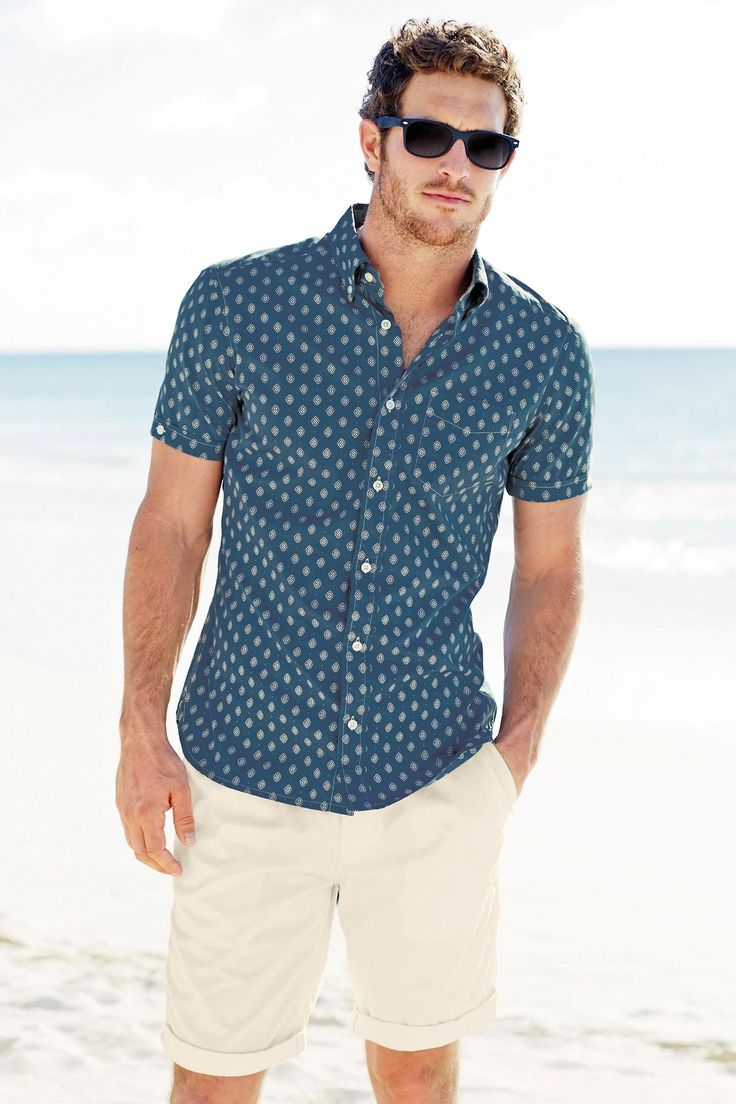 a navy printed short sleeve shirt and tan shorts are all you need for a relaxed beach holiday