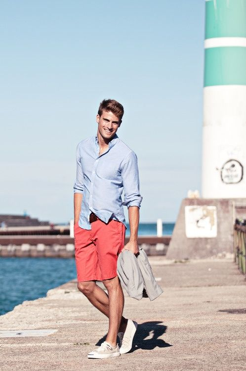 a bleu shirt, coral shorts, tan sneakers and a grey jacket for a relaxed seaside holiday