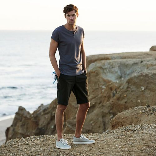 a grey tee, black shorts, grey sneakers for a relaxed and sporty summer holiday look