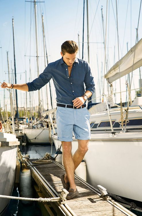 a navy long sleeve shirt, blue shorts and grey moccasins for a stylish and elegant seaside look