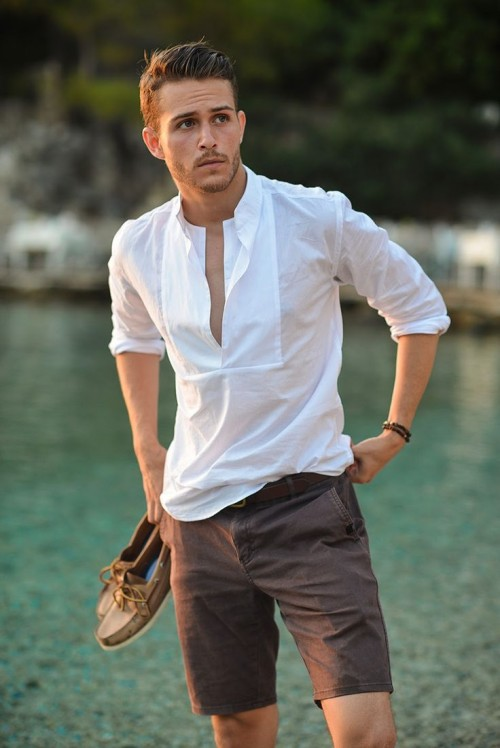 a white long sleeve shirt with a deep cut, brown shorts and tan moccasins for a seaside look