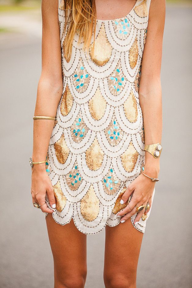 a sleeveless mini gold scallop dress with green touches is a chic piece for a modern party
