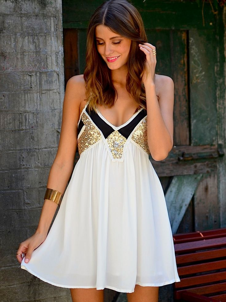 an A line white, black and gold sequin mini dress with spaghetti straps is a cool piece for any party