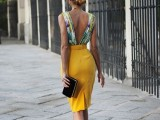 a bold floral top with a cutout back, a sunny yellow fitting skirt, black and white shoes and a black clutch