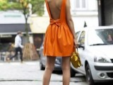 an orange a-line mini dress with an open back, nude shoes and a gold mini bag for a wow look