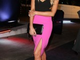 a black sleeveless cutout top, a hot pink skirt wiht a slit, black shoes and a black bag