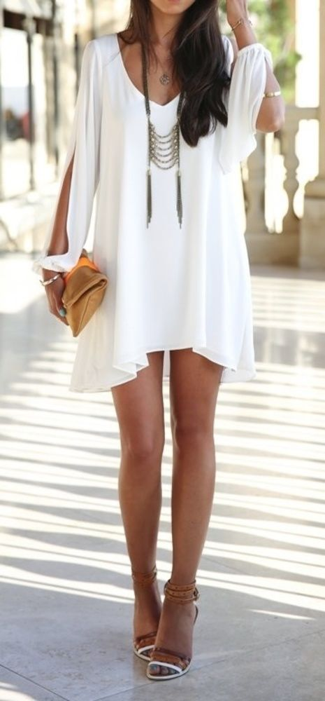 a white mini dress with an asymmetric skirt, cutout sleeves, a statement necklace and a clutch