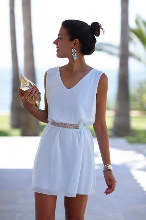 a white sleeveless fitting mini dress with an embellished sash, statement earrings and bracelets plus a metallic clutch