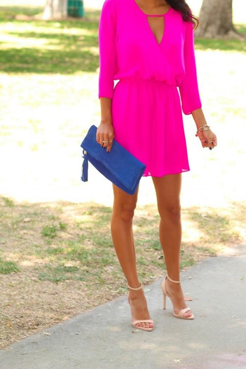a bold hot pink mini dress with long sleeves and a deep cut, tan shoes and a blue clutch