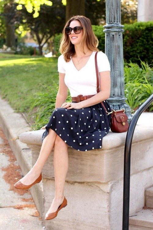 a retro-inspired look with a white top, a polka dot A-line skirt, brown flats, a bag and a belt