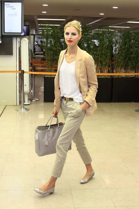 a neutral outfit with grey pants, a white top, embellished flats, a camel blazer and a grey tote