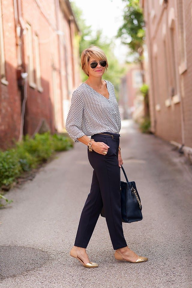 a printed blouse with a V neckline and wide sleeves, navy skinny pants, metallic flats and a black tote