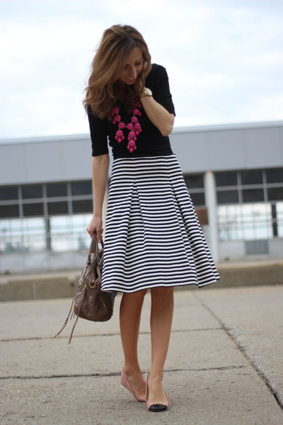 a black top, a striped midi, a statement pink necklace, blush and black flats and a grey bag