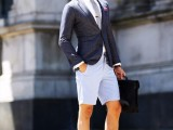 a summer work look with light blue shorts, a white shirt, a grey tie, a navy blazer, brown moccasins and a black bag